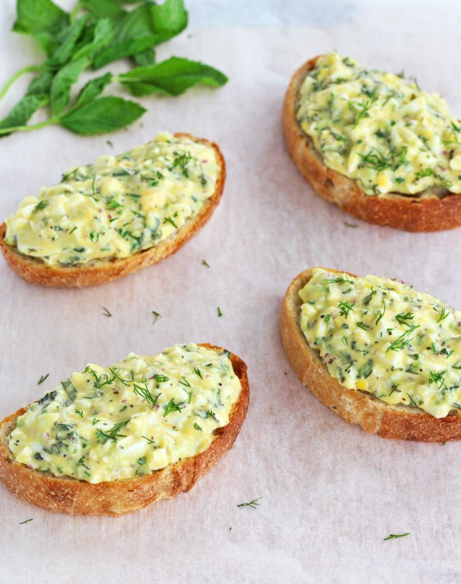 Four herby egg salad tartines sprinkled with fresh dill leaves on top of a nonstick cooking paper background. Mint leaves on stem behind the egg salad tartines.